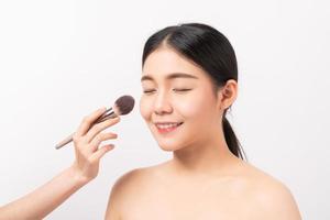 vrouw die make-up krijgt die op witte achtergrond wordt gedaan