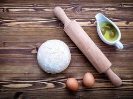 rauw pizzadeeg en deegroller met eieren op een houten achtergrond