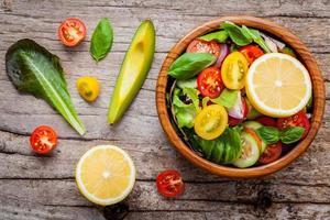 kom met salade in een houten kom foto