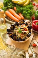 spaghetti en mosselen in een houten kom op een houten bord naast groenten