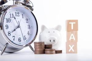 tijd om belasting te betalen. spaarvarken klok, gestapelde munten en houten blok op witte achtergrond. belastingheffing en jaarlijks belastingconcept
