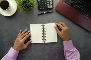 man bladert door een notitieblok op het bureau