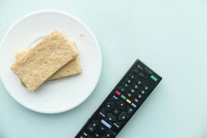 koekjes en tv-afstandsbediening op lichtblauwe achtergrond
