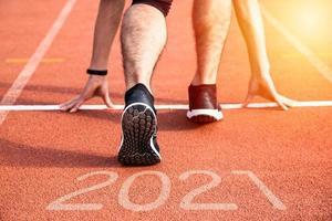 nieuw jaar of begin rechtstreeks concept. close-up van een atleet die naar succes en nieuwe prestaties rent met inscriptie 2021 foto