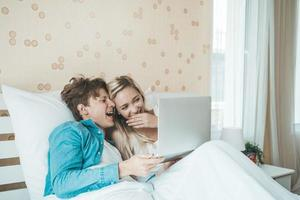 gelukkige paar met laptopcomputer op het bed