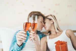 gelukkige paar wijn drinken in de slaapkamer foto