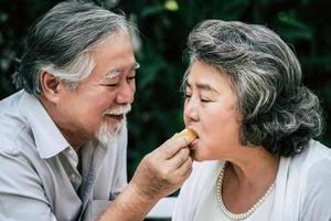 bejaarde echtpaar spelen en eten wat fruit