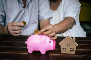 bejaarde echtpaar praten over financiën met spaarvarken