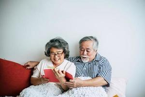 bejaarde echtpaar liggend op het bed en lezen van een boek