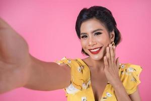 mooie modieuze vrouw die een selfie met haar telefoon neemt