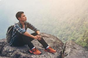 jonge hipster man rust op de bergtop. reizen levensstijl concept.