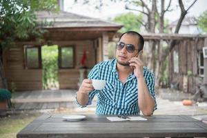 jonge zakenman met behulp van smartphone tijdens het werken in de tuin
