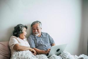 bejaarde echtpaar praten en met behulp van laptop in de slaapkamer