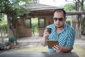 jonge man zit buiten aan een houten tafel en ontspannen met tablet