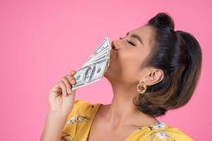 gelukkig modieuze vrouw met geld om te winkelen