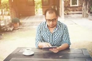zakenman werkt op tablet zittend aan houten tafel thuis