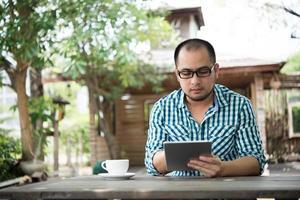 zakenman werkt op tablet zittend aan houten tafel thuis foto