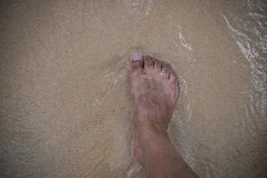 man's voet staande op het strand