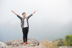 wandelaar met rugzak staande op de top van een berg met opgeheven handen