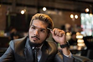 knappe zakenman na te denken over werk tijdens het werken in café