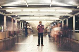 knappe bebaarde man met rugzak staande op straat 's nachts reizen foto