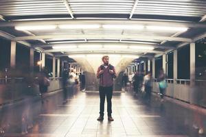 knappe bebaarde man met rugzak staande op straat 's nachts reizen