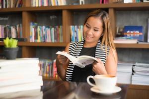 Aziatische vrouw die een boek in bibliotheek leest foto