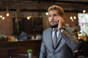 knappe zakenman praten over de telefoon tijdens een pauze in café foto