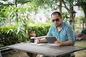 zakenman werken op tablet en schrijven zittend aan houten tafel thuis