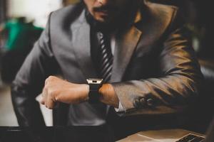 close-up van de hand van de zakenman kijken naar handhorloge foto