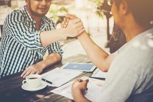 close-up van twee zakenmensen handen schudden zittend op de werkplek