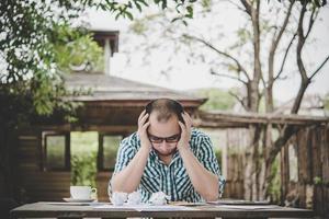 benadrukt zakenman met papieren en grafieken om thuis aan tafel te zitten
