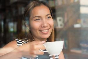 Aziatische vrouw ontspannen met koffie in café