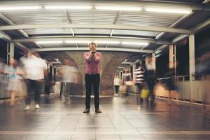 hipster bebaarde man die op de vloer met mensen bewegende achtergrond