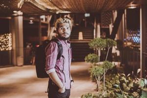 knappe bebaarde man met rugzak staande op straat tijdens het reizen 's nachts