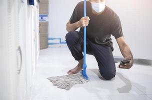 Aziatische man schoonmaken met een dweil foto