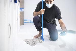 Aziatische man die de vloer dweilt foto