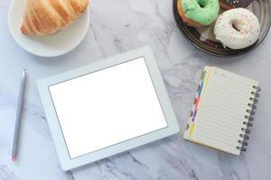 bovenaanzicht van een tablet met donuts op marmeren achtergrond