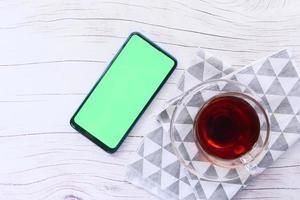 bovenaanzicht van een slimme telefoon en thee op tafel
