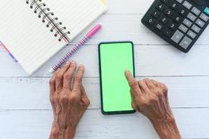 oude vrouw met behulp van een slimme telefoon op een bureau