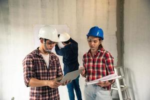 jonge Aziatische ingenieurs die een huis bouwen foto