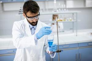 onderzoeker die met blauwe vloeistof bij laboratoriumglas werkt