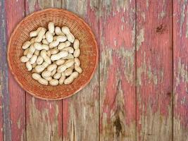 pinda's in rieten mand op rode houten achtergrond foto