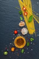 verse spaghetti-ingrediënten op een donkere achtergrond foto