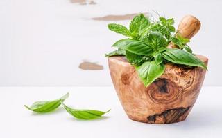 kruiden in een houten vijzel op armoedig wit foto