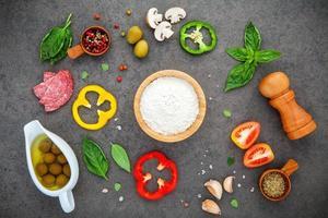 bovenaanzicht van pizza-ingrediënten op een donkergrijze achtergrond foto