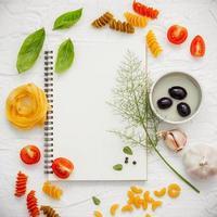 bovenaanzicht van een notitieboekje met Italiaanse ingrediënten