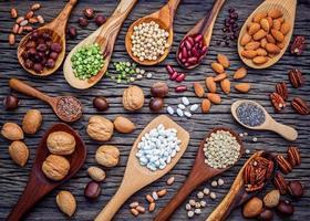 peulvruchten en noten in lepel op een donkere houten achtergrond foto
