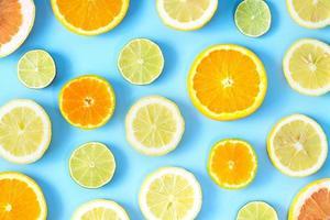 verzameling van verse limoen, citroen, sinaasappel, citrus, grapefruitplak op blauwe achtergrond. foto