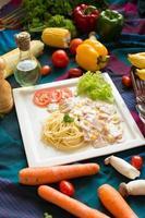 pasta carbonara met spek en Parmezaanse kaas op een witte plaat met groenten op kleurrijk tafelkleed